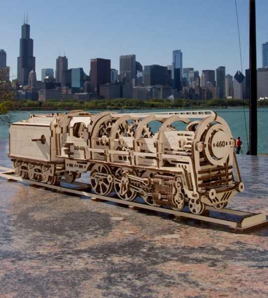 Ugears mechanischer Modellbausatz Dampflokomotive mit dem Anhänger und 3D-Holzpuzzle. Selbstfahrender Konstruktionsmodellsatz von Zug und Teil der Eisenbahn. Originelles Geschenk für Jungen und Mädchen und Smart-Hobby für Erwachsene.