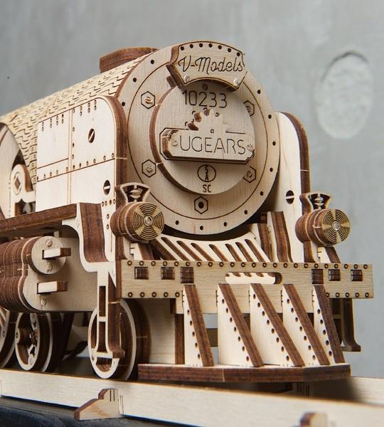 Ugears mechanischer Modellbausatz V-Express Dampflokomotive mit Tender und 3D-Holzpuzzle für die Selbstmontage. Lokomotivmodell mit Getriebe und Schwungrad, die Arbeit der Zylinder-Kolben-Anordnung - die wichtigsten mechanischen Blöcke einer echten Dampfmaschine. Originelles Geschenk für Jungen und Mädchen und intelligente Hobby für Erwachsene.